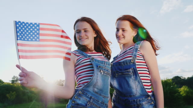 Two cute redheaded teenage girls with an American flag. Smile, look at the camera. 4K slow motion video Two redheaded teen girls with an American flag. Smile, look at the camera family 4th of july stock videos & royalty-free footage