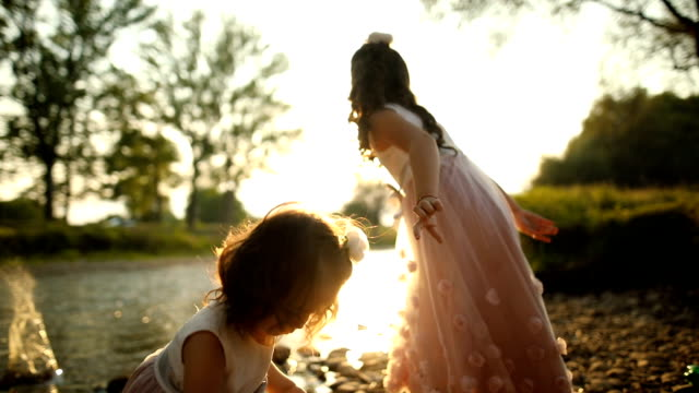 Two cute sisters.Sunset at the River video