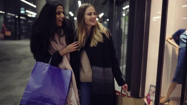 två söta unga unga kvinnor, tunga laddad med julklappar, shopping, medan promenader längs skyltfönster och välja och beundrar objekt. - spendera pengar bildbanksvideor och videomaterial från bakom kulisserna