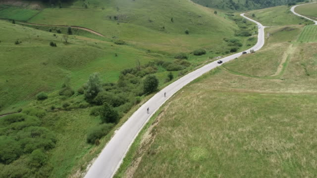 two cyclist riding their bicycles down a mountain road and preparing themselves for a triathlon, the shot is moving - triatleta video stock e b–roll