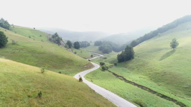 due ciclisti in bicicletta lungo una strada di montagna - triatleta video stock e b–roll