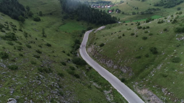 two cyclist riding their bicycles down a road and heading to the village - triatleta video stock e b–roll