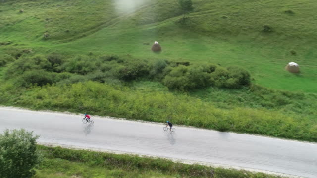 two cyclist riding their bicycles down a road through the mountains - triatleta video stock e b–roll