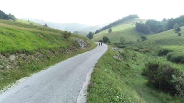 two cyclist riding their bicycles down a road - triatleta video stock e b–roll