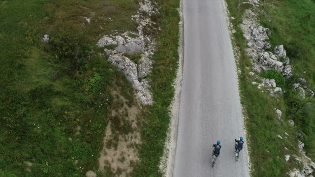 two cyclists training and preparing themselves for triathlon contest in the mountains - triatleta video stock e b–roll