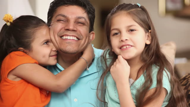 Two daughters kiss their dads cheeks. video