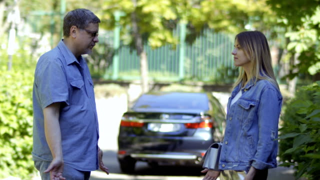 two deaf-mute people talking at blurred car background in park - chiedere scusa video stock e b–roll
