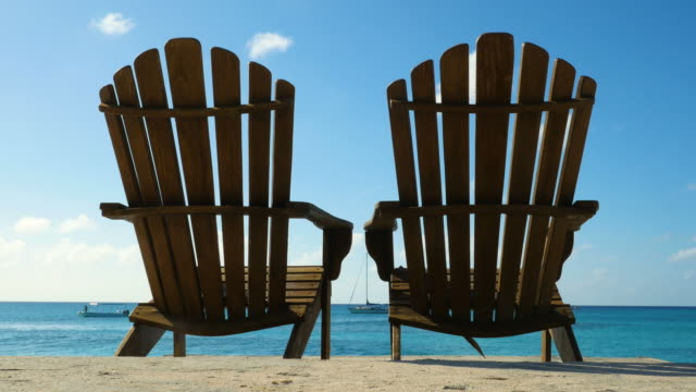Two deckchairs on the beach of the Caribbean Two deckchairs on the beach of the Caribbean with a view of the sea turks and caicos islands stock videos & royalty-free footage