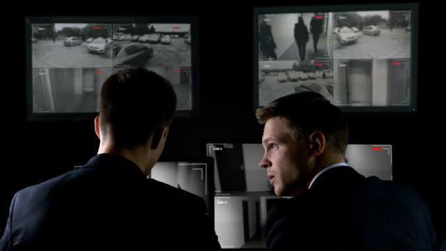 Two detectives checking surveillance camera records after crime, investigation Two detectives checking surveillance camera records after crime, investigation detective stock videos & royalty-free footage