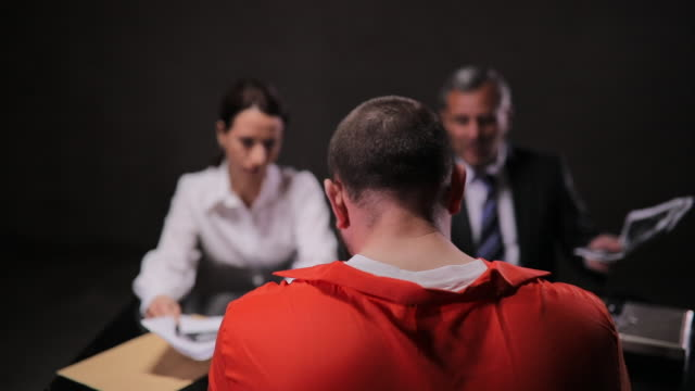 Two detectives talking to a prisoner in interrogation room
