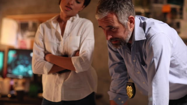Two detectives working in the station at night