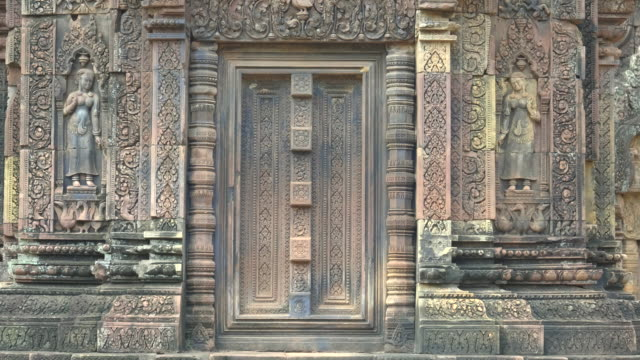 two devata carved in a wall of banteay srei temple