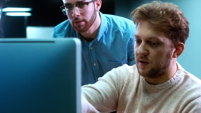 Two developers working on a project and communicating together at trendy start up office, discussing project on a computer screen video