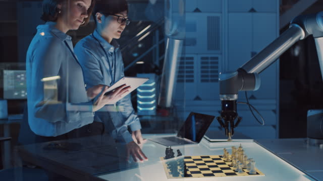 vídeos de stock e filmes b-roll de two development engineers are discussing and testing an artificial intelligence interface by playing chess with a futuristic robotic arm. they are in a high tech modern research laboratory. - xadrez