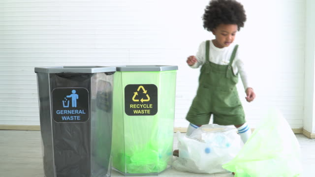 Two different ethnic children help to seperate plastic bottle into recyclable bin