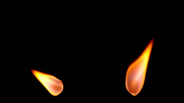 stockvideo's en b-roll-footage met twee verschillende vlam kaarsen op een zwarte achtergrond. - kaars