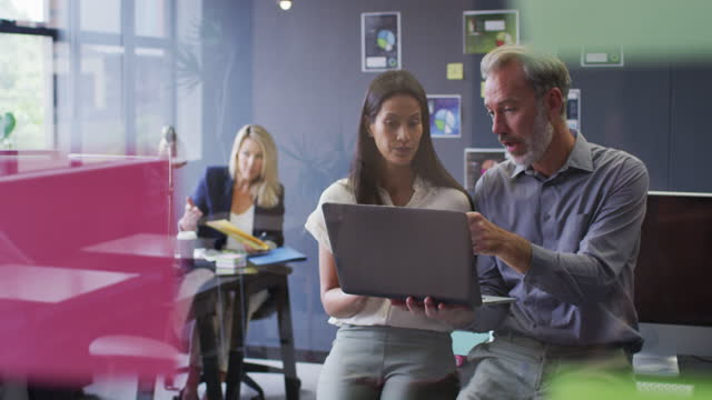Two diverse business people using laptop talking in office and colleague working behind