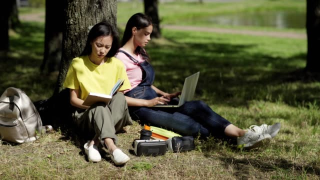 Two diverse college students sitting in shade under tree leaning on trunk in park. Asian girl reading book, her Caucasian friend typing on laptop. Backpacks, binder and vr headsets near them