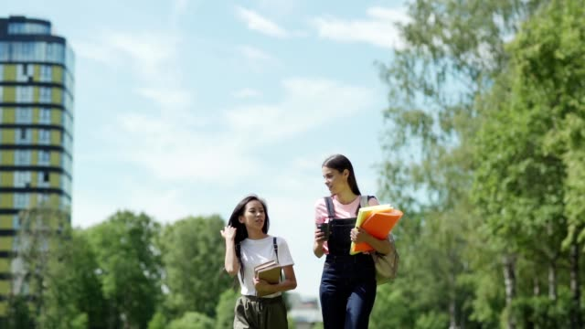 due diverse studentesse universitarie, asiatiche e caucasiche, con libri di testo e raccoglitori che parlano mentre camminano per le lezioni nel campus al rallentatore, colpo di tre quarti di lunghezza - bassino video stock e b–roll
