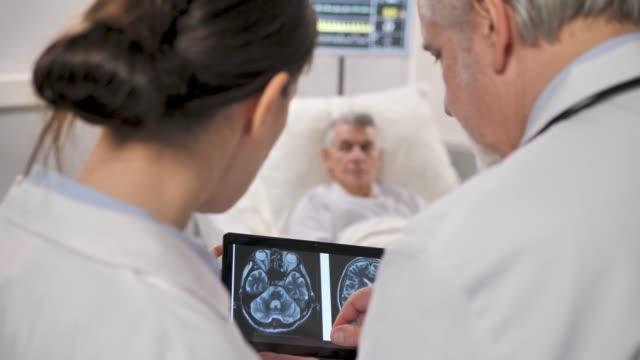 vídeos de stock e filmes b-roll de two doctors check xrays on tablet blurred patient man in the background - instrumento para diagnóstico
