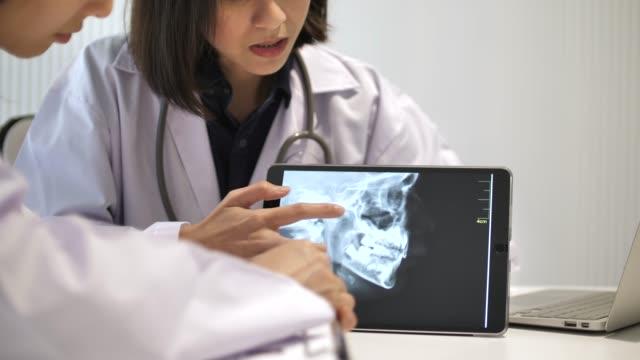 två läkare samråd på röntgenbilden med digital tablett - two dentists talking bildbanksvideor och videomaterial från bakom kulisserna
