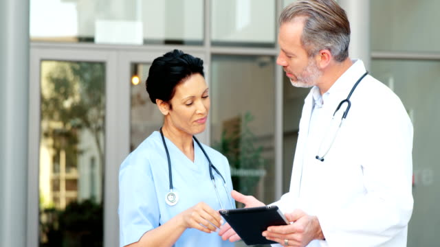 Two doctors discussing over digital tablet video