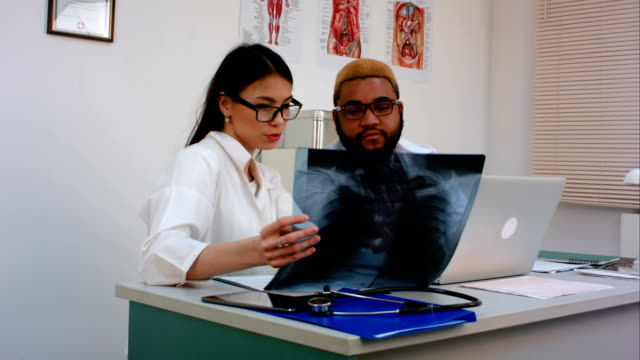 Two doctors discussing X-ray image while using computer