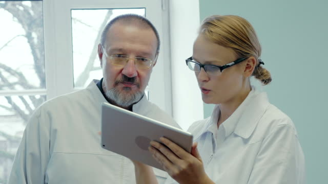 Two doctors having professional talk using touch pad video