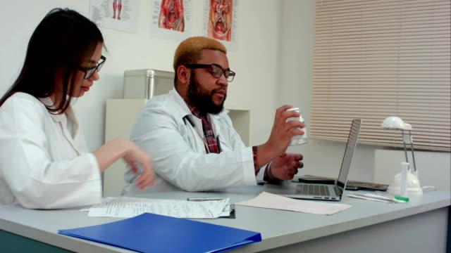 vidéos et rushes de deux médecins prescrivant des pilules via webcam - pots de bureau