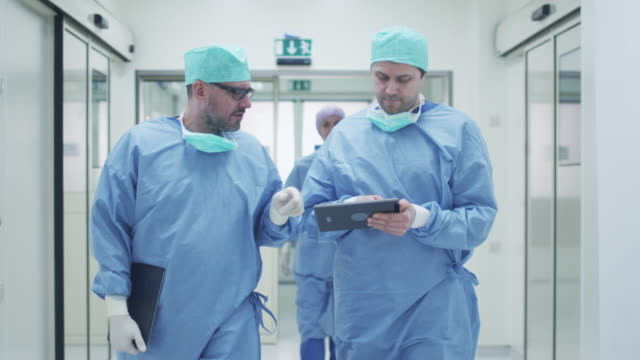 兩位醫生走過醫院聊天。手拿著平板電腦。 - surgeon 個影片檔及 b 捲影像