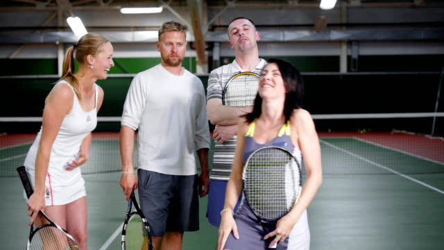 Two doubles teams after the tennis match. Two male players and two female players. They standing together, smiling and laughing. Friendly competition video