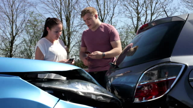 Two Drivers Exchange Insurance Details After Accident Male and female drivers swapping insurance details using mobile phones after accident.Shot on Canon 5d Mk2 with a frame rate of 30fps car accident stock videos & royalty-free footage