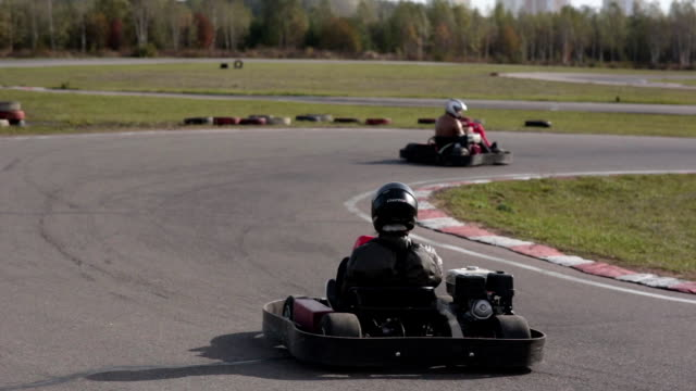 Two drivers in karts are moving very slowly on a ride. Go kart track Go kart track. Two drivers in karts are moving very slowly on a ride go cart stock videos & royalty-free footage