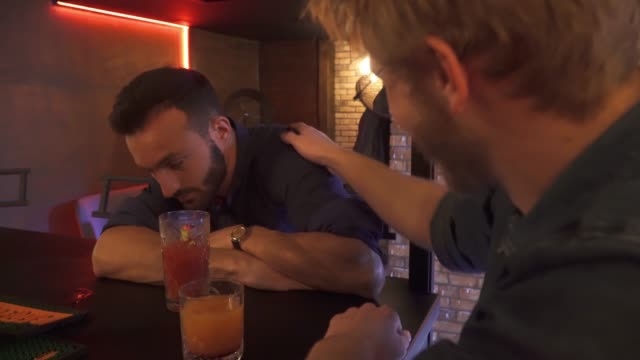 Two drunk friends sit at the bar Two drunk friends sit at the bar. Two friends are relaxing in the club in the evening. Red-haired guy in glasses with a beard takes a cocktail. Leisure and communication concept. margarita stock videos & royalty-free footage