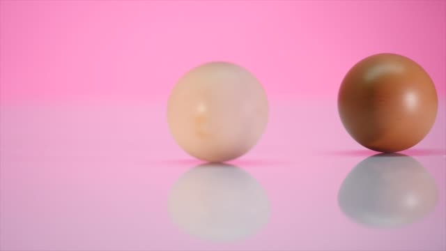 Two eggs are spinning on a table on a pink background video