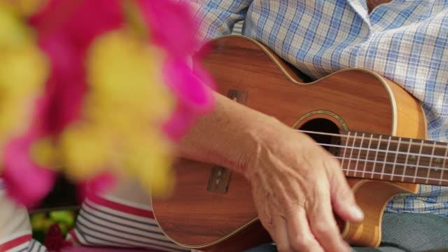 två äldre kvinnor spelar ukulele - akustisk gitarr bildbanksvideor och videomaterial från bakom kulisserna