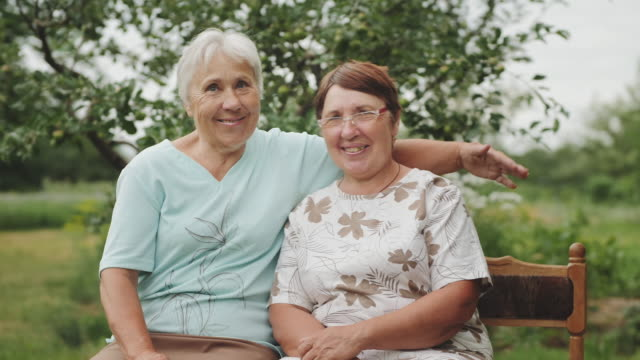 Two elderly women smiling looking at the camera Grandmother embracing sitting on a bench in the garden. Two elderly women smiling looking at the camera. Camera moves in slow motion. cousin stock videos & royalty-free footage