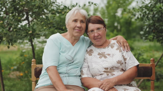 Two elderly women smiling looking at the camera Older women embracing sitting on a bench in the garden. Two people smiling looking at the camera. The camera moves in slow motion. cousin stock videos & royalty-free footage