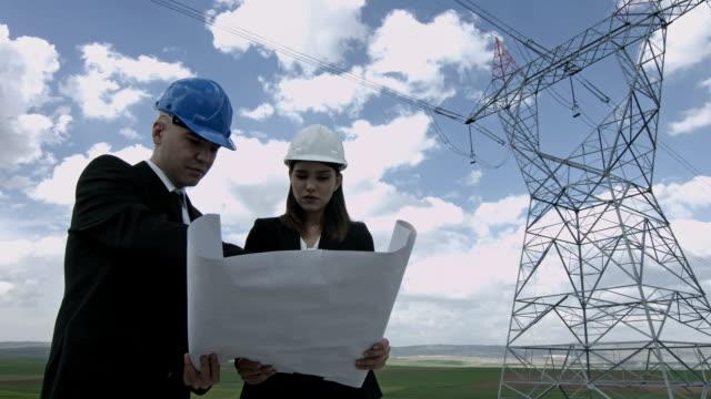 two electrical engineers working on technical drawing - rådig bildbanksvideor och videomaterial från bakom kulisserna