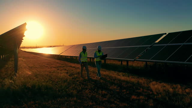 Two electricians passing by long rows of solar panels at sundown video