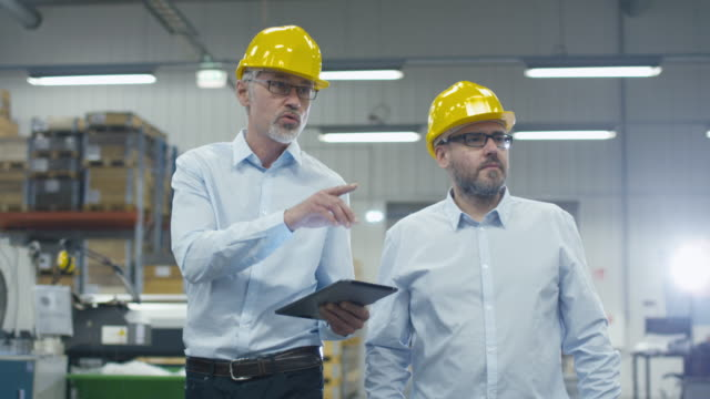 Two employees are walking with tablet computer at logistics center warehouse.