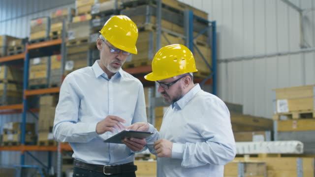 vídeos de stock e filmes b-roll de two employees are walking with tablet computer at logistics center warehouse. - experiência científica