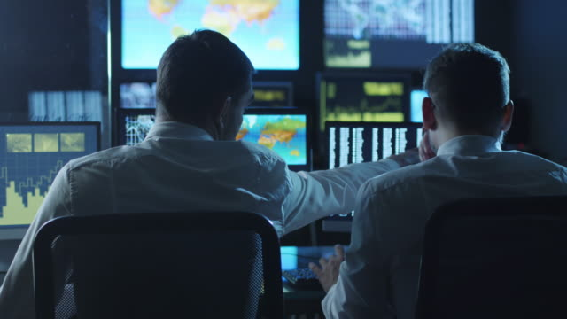 Two employees are working on computers in a weather forecast center filled with display screens. Two employees are working on computers in a weather forecast center filled with display screens. Shot on RED Cinema Camera in 4K (UHD). meteorology stock videos & royalty-free footage