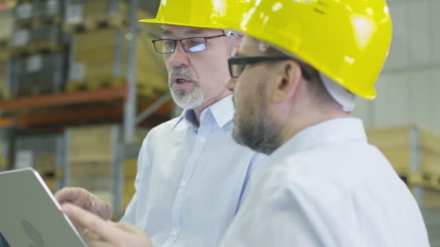 Dos empleados en el almacén del centro logístico están discutiendo el trabajo mientras sostienen un ordenador portátil. - vídeo