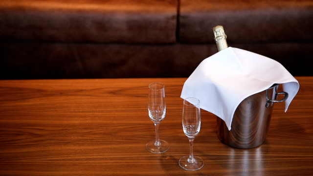 Two empty wineglasses and champagne bottle on the table