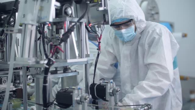 vídeos de stock, filmes e b-roll de dois engenheiros operando e verificando o status da linha de produção em uma fábrica de máscaras faciais protetoras - equipamento médico