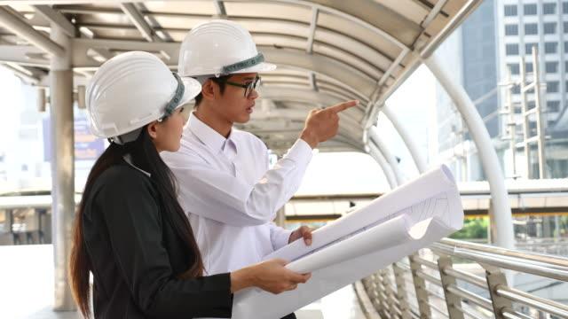 stockvideo's en b-roll-footage met twee ingenieur werknemers bespreekt een bouwproject - oost azië
