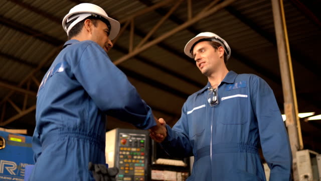 Two engineering in production plant as team discussing