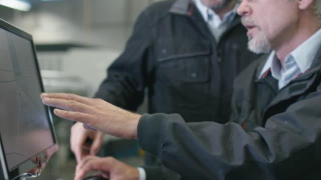 2人のエンジニアが工場のデスクトップコンピュータで作業しています。 ビデオ