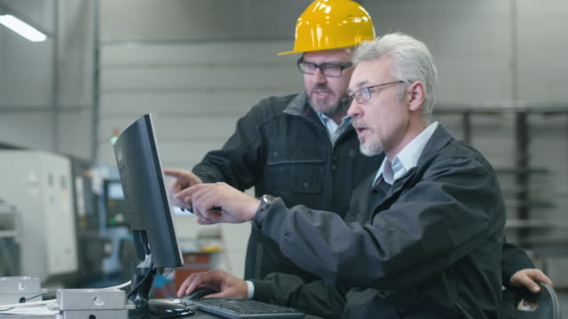 Deux ingénieurs travaillent sur un ordinateur de bureau dans une usine. - Vidéo